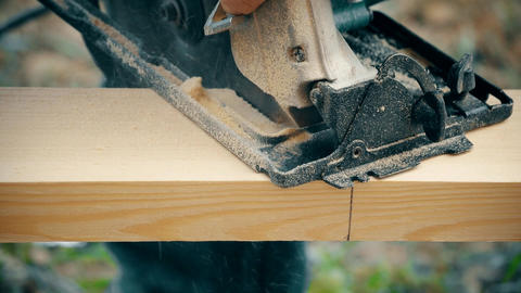 Cutting a wooden plank with portable circular saw Live Action