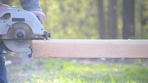 Sawing wooden beam with portable circular hand saw Footage