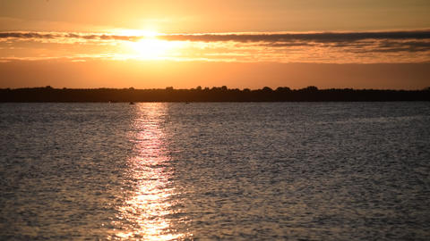 Sunrise over water with orange and yellow clouds Footage