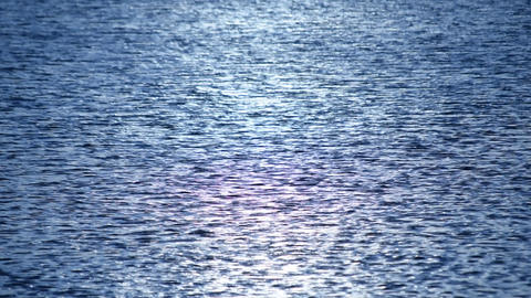 Dark blue water surface with ripples and sun path Footage