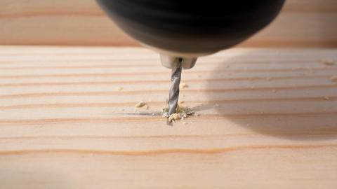 Drilling a hole in a pine wood plank with a drill bit Footage