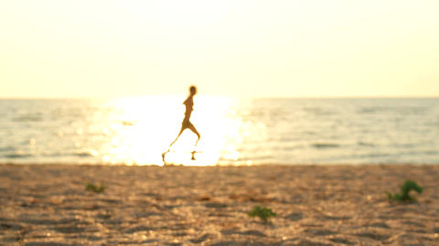 Man runs on beach at dawn in slow motion Footage