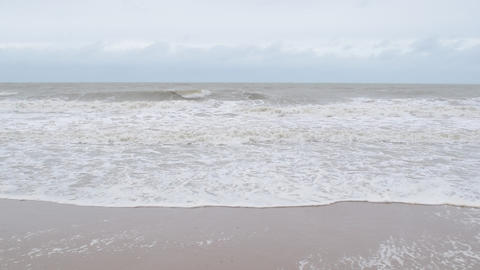 Sandy sea shore during overcast weather with waves Footage