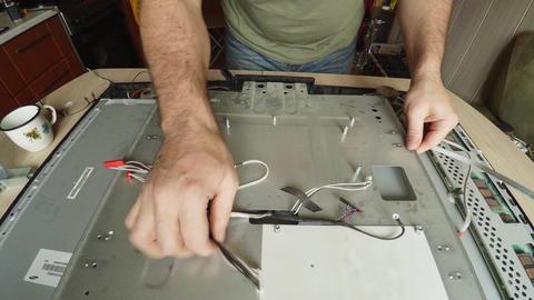Electronic Engineer dismantles, repairs TV. 4K Footage