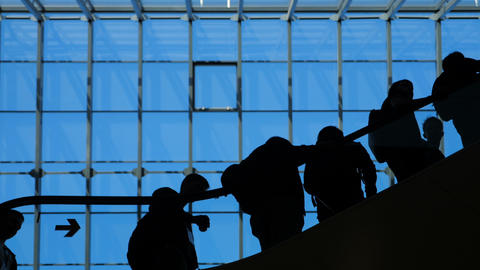 The glass window airport ecsalator with moving silhouette of people Footage