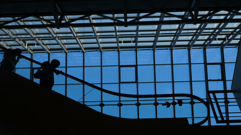 The glass window airport ecsalator with moving silhouette of people Image
