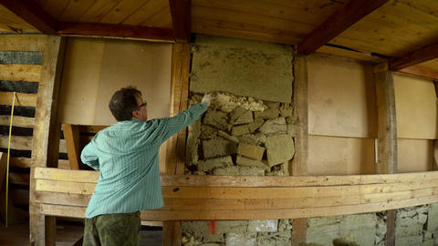 The worker removes the glass wool from the wooden wall. 4K Live Action
