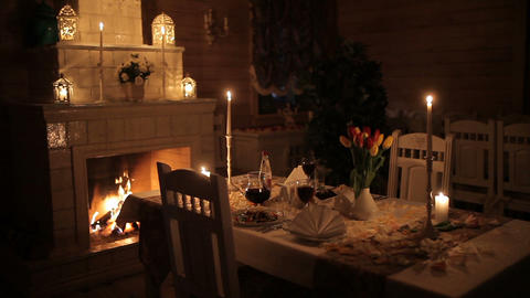 A loving couple dines by candlelight near the fireplace Footage