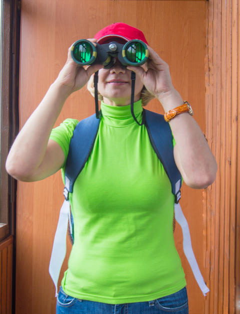 Happy woman tourist with backpack looking through binoculars, search purpose フォト