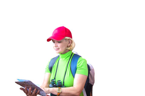 Happy tourist woman in green t-shirt and red cap with backpack looking at map フォト