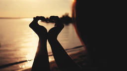 Woman making heart symbol with her hands during sunset on beach. Slow motion Footage