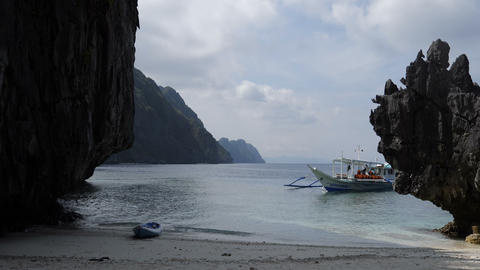 Islands, boat and clear water at Matinloc Shrine beach Live Action