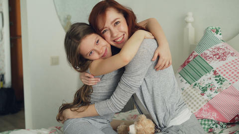 Portrait of cute smiling girl embracing her happy mother looking at camera Footage
