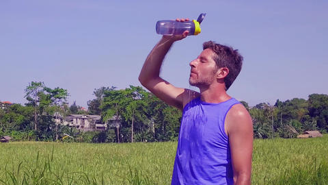 Steady cam on runner man drinking water thirsty after running work out Footage