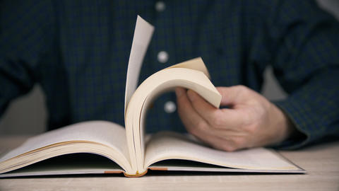 Man holding pages and browsing antique old book Live Action