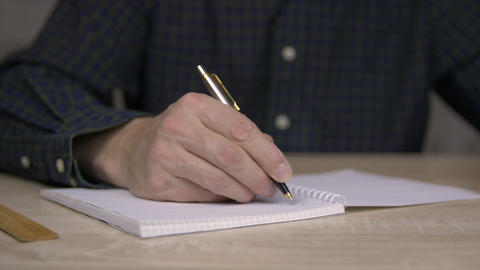 Man studying and writing in copybook with pen. Close up man hand with pen write Live Action