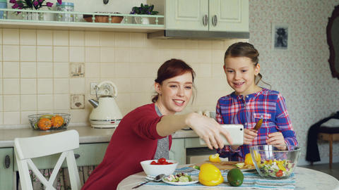 Smiling mother making selfie photo together with young cute daughter cooking Footage