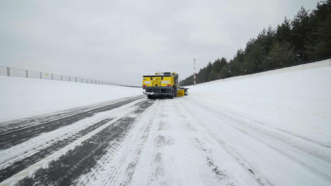 Snow and ice removal truck removes snow from the road with big bucket in snowy Footage