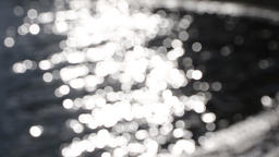 Out of focus bokeh of sun glares reflected in water Footage