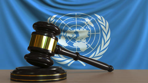 Judge's gavel and block against the flag of the United Nations. Court conceptual Footage