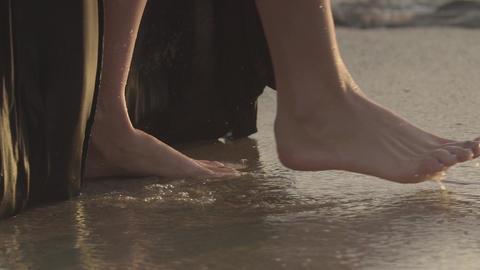 SLOW MOTION: female legs in the sea waves. Sandy beach Footage