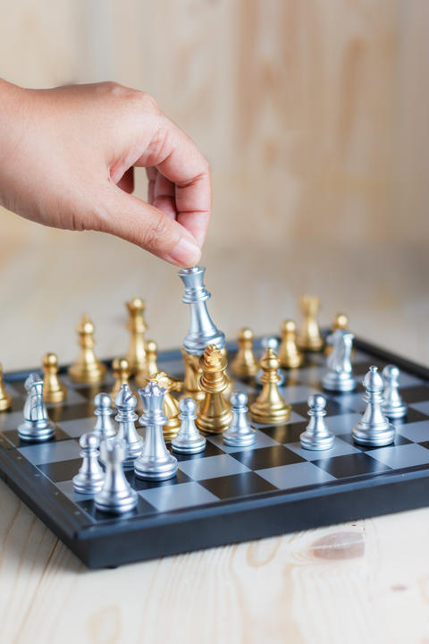 Hand of woman moving king silver chess to kill golden king chess Photo
