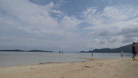 Tourists walk on starfish island on small beach by boat Live Action