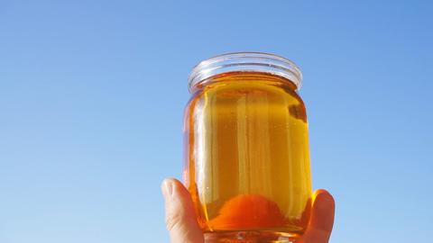 A honey jar against a blue sky background GIF