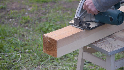 Hands sawing wooden beam lengthwise with a circular hand saw Footage