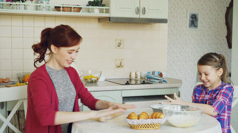 Happy mother and cute daughter cooking together talking in the kitchen at home Footage