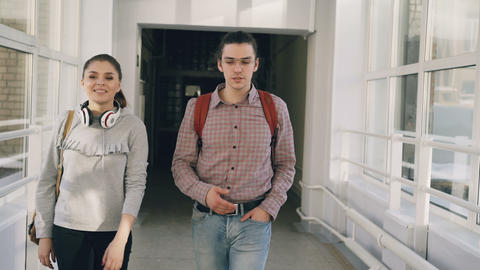 Two female and male students are walking in university hall discussing something Footage