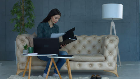Worried woman working on her finances at home Footage