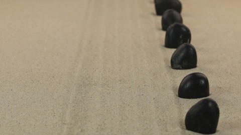 Approximation of black stones standing on lines from sand. Dolly Footage