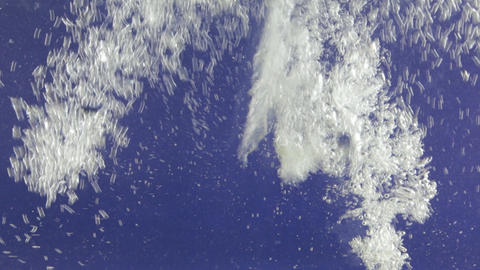 Stream of white bubbles in blue water. Pouring water splashes and creates Footage