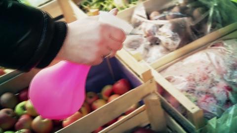 A woman sprays fruit on a street market ビデオ