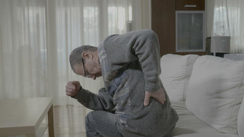 Elderly ill man with rheumatism stretching and massaging his back having a Footage