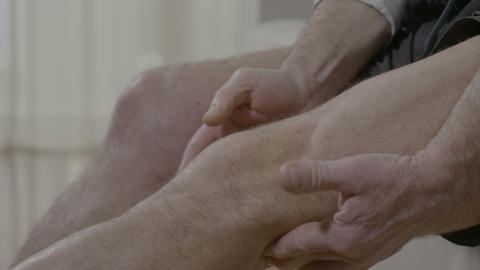 Old man massaging his arthritic knee having joint ache at home Footage