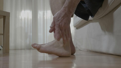 Patient mature man with arthritis sitting on bed and rubbing his ankle and foot Footage