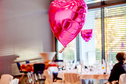 Pink festive balloons shape of heart with the party guests in the background Fotografía