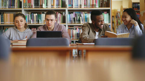 Multi-ethnic group of students siting in library with books and laptop on table Footage