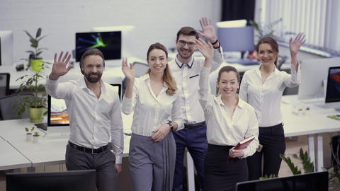 Team of businesspeople waves hands to camera Footage