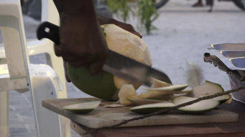 Man cuts off pieces from a young fresh coconut. Maldives video Archivo