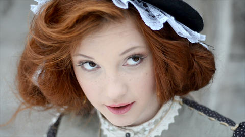 Beautiful red-haired girl in a hat looks up Live Action