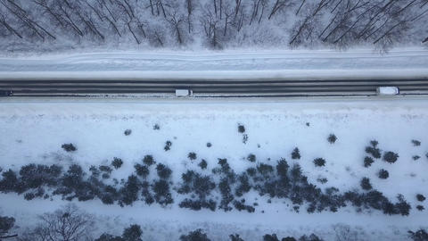 Aerial view on cars driving through winter forest road. Scenic winter landscape Footage