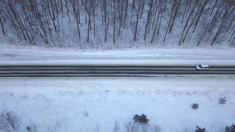 Aerial view on car driving through winter forest road. Scenic winter landscape Live Action