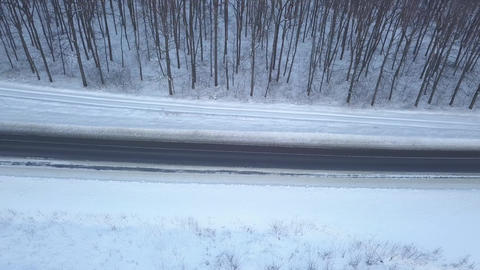 Aerial view on cars driving through winter forest road. Scenic winter landscape Live Action