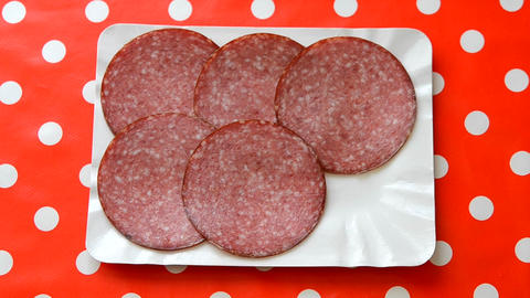 Person put slices of smoked sausage. Close-up top view Footage