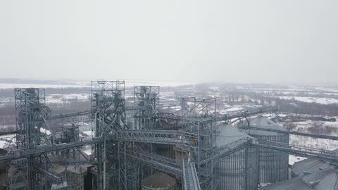 Flight under granaries and elevators or oil storage on winter background Footage