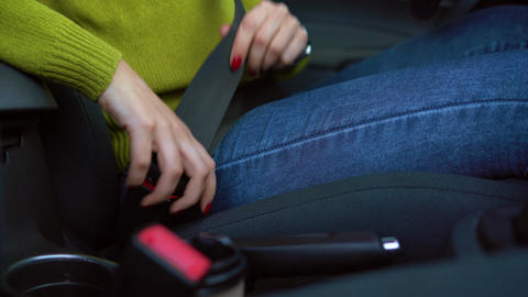 Female hand fastening car safety seat belt while sitting inside of vehicle Footage