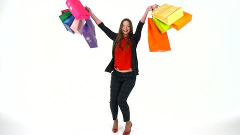 Female shopper holding multicolored shopping bags on white background in studio Archivo